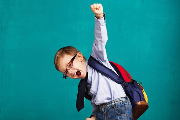 Child with back pack punching fist into air. Chiropractic backpack tips