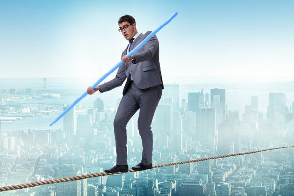 Man in suit balancing on tight rope. Neck Pain and Dizziness