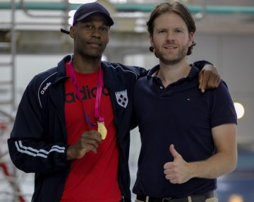 Swimmer Masai Zebechaka holding his gold medal at the pool with Sports Chiropractic Dr Wesley Trowse standing next to him