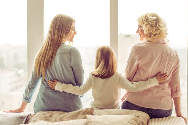 Three women sitting on a bed. Grandmother, daughter and granddaughter